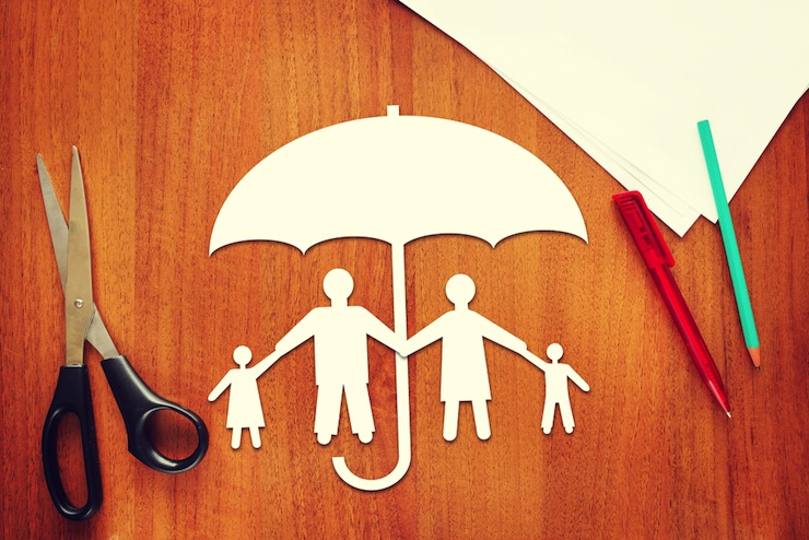 paper family standing under umbrella